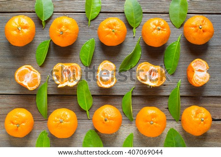 fresh mandarins with leafs on old wooden table - stock photo
