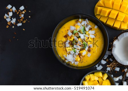 fresh mango and coconut smoothie bowl on black background, top view, square image