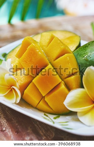 fresh mango in the plate on a wooden tabel with tropical background. Soft focus.