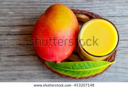 Fresh mango smoothie,ripe mango fruit and mango tree leaf in a small basket on old wooden background.Healthy food,diet or vegan food concept.Top view. - stock photo