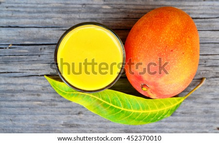 Fresh mango smoothie,ripe mango fruit and mango tree leaf on old wooden table background.Healthy food,diet or vegan food concept.Top view. - stock photo