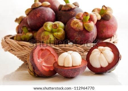 Fresh mangosteens fruit and cross section showing the thick purple skin and white flesh of the queen of fruits. - stock photo