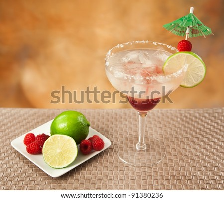 fresh margarita with limes on a plate and salt rim