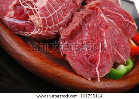 fresh meat on wood with sliced pepper