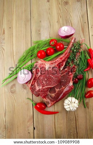 fresh meat : raw beef spare ribs with thyme , red chili pepper , garlic , dill, and cherry tomato on wooden board - stock photo