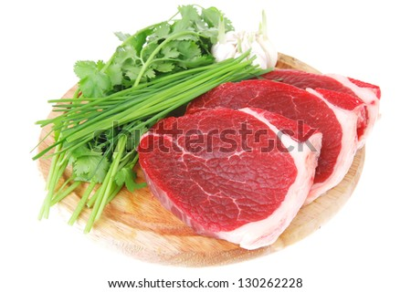 fresh meat : raw uncooked fat lamb pork fillet with green stuff and garlic on wooden plate isolated over white background - stock photo