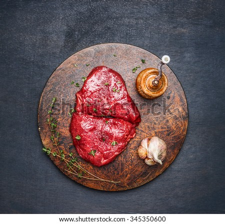 Fresh meat steak with ingredients on round cutting board on dark wooden background, top view - stock photo