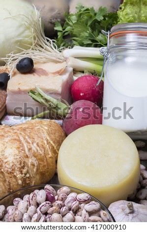 fresh meat with healthy vegetables, milk and bread placed on a wooden table - close-up - stock photo