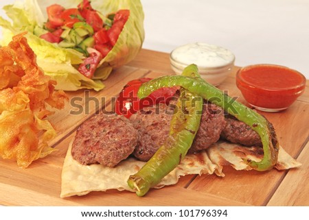 fresh meatballs on wooden plate with salad and garniture