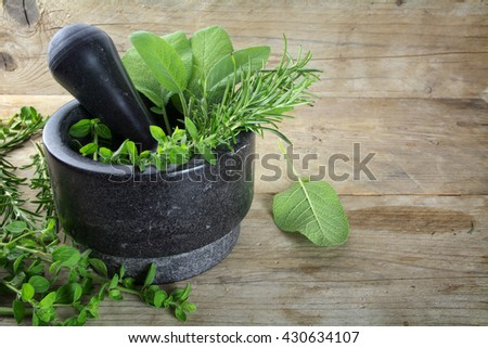 fresh Mediterranean herbs, oregano, rosemary and sage in a mortar made of black granite on a rustic wooden board, copy space, selected focus, narrow depth of field