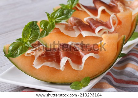 Fresh melon with prosciutto and basil close-up on the table. horizontal  - stock photo