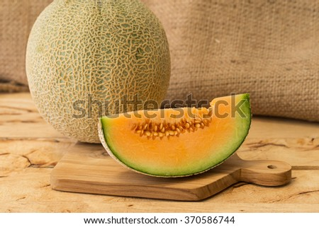 Fresh melons sliced on old wooden table. - stock photo