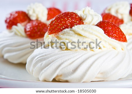 Fresh meringue with thick cream and strawberries on a plate - stock photo