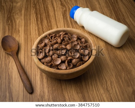 Fresh milk and cornflakes in wood bowl on a wooden table background. Organic healthy food rich in minerals and vitamins. Eco food for breakfast. - stock photo