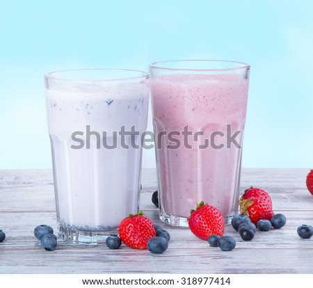 Fresh milk, blueberry and strawberry drinks on wooden table, assorted protein cocktails with fresh fruits.  - stock photo
