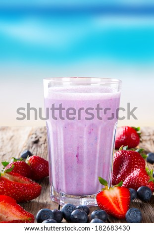Fresh milk, blueberry drink on wodeen table, assorted protein cocktail with fresh fruits. Summer drink on the beach and blue sky. - stock photo
