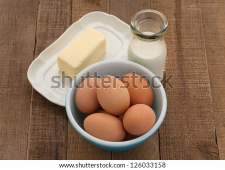 Fresh Milk, Butter, and Brown Eggs in Rustic Setting on Weathered Wood for a Vintage Feel - stock photo