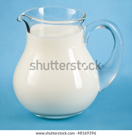 Fresh milk in glass jug, on blue surface background  - stock photo