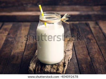 Fresh milk in the glass jar on the table  - stock photo