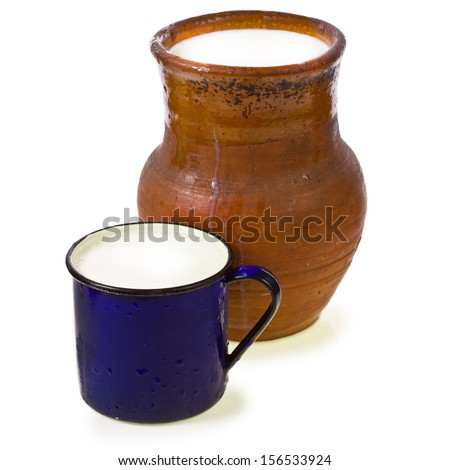 fresh milk is poured into an old clay jug and always have the blue vintage enamel mug close-up isolated on white background - stock photo
