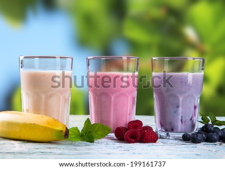 Fresh milk, raspberry and blueberry drinks on wooden table, assorted protein cocktails with fresh fruits. Natural background.
