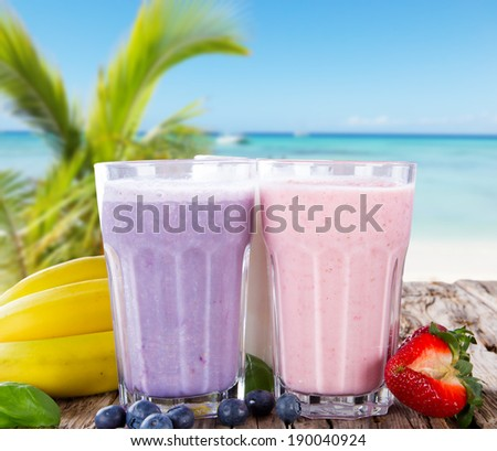 Fresh milk, strawberry and blueberry drinks on wodeen table with tropical beach, assorted protein cocktails, fruits. - stock photo
