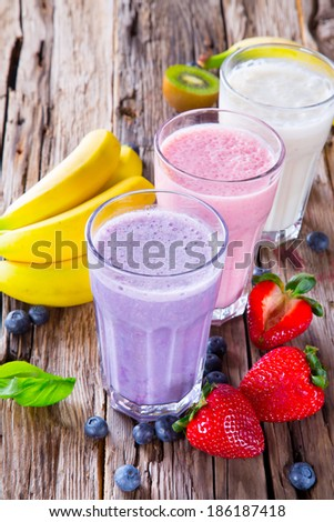Fresh milk, strawberry, blueberry and banana drinks on wodeen table, assorted protein cocktails with fruits.  - stock photo