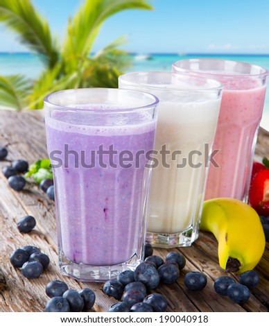 Fresh milk, strawberry, blueberry and banana drinks on wodeen table with tropical beach, assorted protein cocktails, fruits. - stock photo