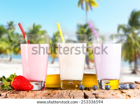 Fresh milk, strawberry, blueberry and banana drinks on wooden table, assorted protein cocktails with fresh fruits and tropical beach.  - stock photo