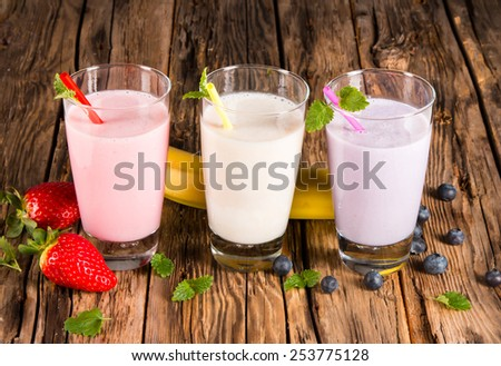 Fresh milk, strawberry, blueberry and banana drinks on wooden table, assorted protein cocktails with fresh fruits. - stock photo