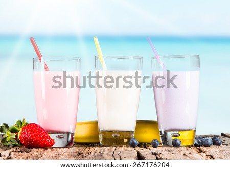 Fresh milk, strawberry, blueberry and banana drinks on wooden table, assorted protein cocktails with fresh fruits. Tropical beach background - stock photo