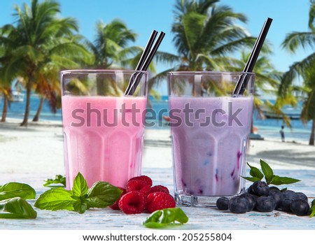 Fresh milk, strawberry, blueberry and banana on wooden table, assorted protein cocktails with fresh fruits. Natural background. Tropical beach.  - stock photo
