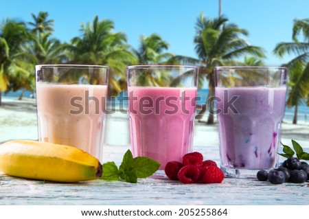 Fresh milk, strawberry, blueberry and banana on wooden table, assorted protein cocktails with fresh fruits. Natural background. Tropical beach.