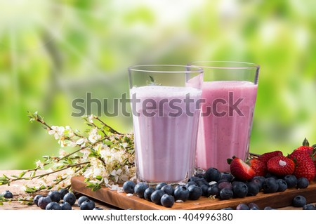 Fresh milk, strawberry, blueberry drinks on wooden table, assorted protein cocktails with fresh fruits.  - stock photo