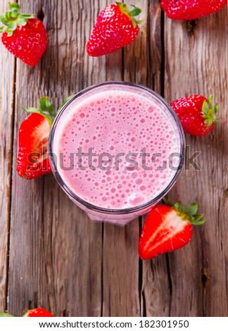 Fresh milk, strawberry drink on wodeen table, assorted protein cocktail with fresh fruits. - stock photo
