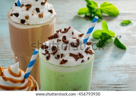 Fresh milkshake for hot summer consists of the combination of ice cream with milk and such ingredients as green apples with mint, chocolate chips. Blurred background. - stock photo