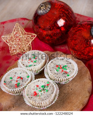 Fresh mini cookies and cream cheesecakes in muffin forms with red Christmas tree balls - stock photo
