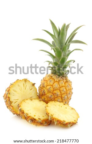 fresh mini pineapple fruit and a cut one on a white background - stock photo
