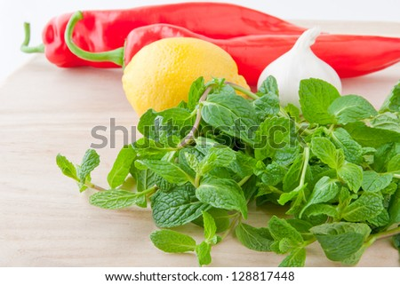 Fresh mint leaves, lemon, bell pepper and garlic for salad or salsa on wooden board. selective focus, shallow dof - stock photo