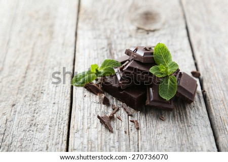 Fresh mint with chocolate on grey wooden background