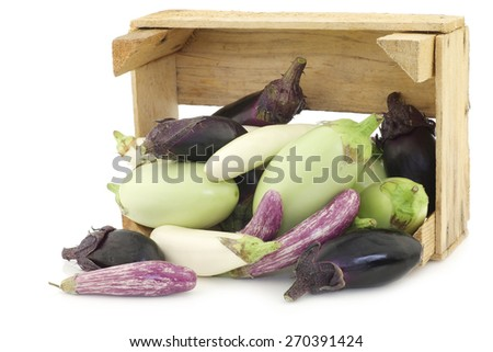 fresh mixed aubergines(Cucurbita pepo), and a cut one in a wooden crate on a white background - stock photo