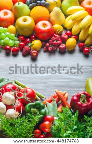 Fresh mixed fruits and vegetables on wooden board, concept of healthy eating and diet - stock photo