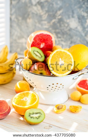 Fresh mixed fruits in bowl on light backgound