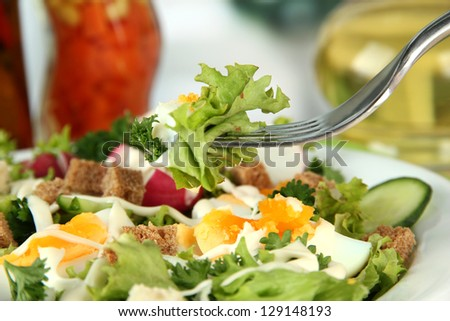 Fresh mixed salad with eggs, salad leaves and other vegetables, on bright background