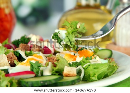 Fresh mixed salad with eggs, salad leaves and other vegetables, on bright background - stock photo