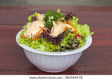 Fresh mixed salad with eggs, salad leaves and other vegetables, on the red table - stock photo