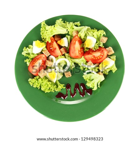 Fresh mixed salad with eggs, tomato, salad leaves and other vegetables on color plate, isolated on white