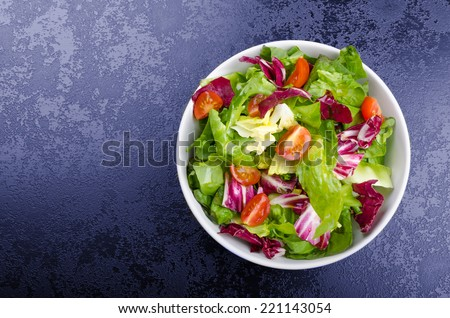 Fresh mixed salad with endive and cherry tomatoes on black plate dining, pouring olive oil - stock photo