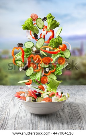 Fresh mixed vegetables falling into a bowl of salad - stock photo