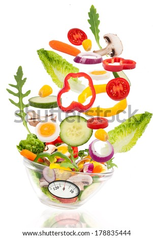Fresh mixed vegetables falling into a bowl of salad with analogous weight scale. Diet concept